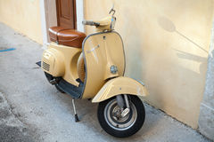 Classic yellow Vespa scooter stands in a town Stock Photo