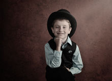 Classic Young Boy Wearing Fashion Clothes. A young boy is dressing up in a black top hat and business suit with a textured isolated background for a vintage or Stock Photography