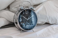 Classical alarm clock on bed Royalty Free Stock Images