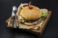 Classical American fresh juicy burger with chicken and ham on a wooden tray with a spicy chili sauce. Beautiful photo on a dark ba Royalty Free Stock Image
