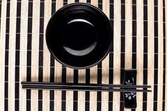Classical asian chopsticks and bowls at bamboo mat Royalty Free Stock Image