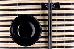 Classical asian chopsticks and bowls at bamboo mat Royalty Free Stock Photos