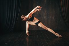 Classical ballet dancer in black practice training. On the stage. Graceful ballerina poses in studio Stock Images