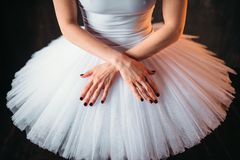 Classical ballet dancer in dress and cross hands. Classical ballet dancer body in white dress and cross hands, black background. Elegance ballerina poses Royalty Free Stock Image