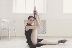 Classical Ballet dancer makes stretching in class Royalty Free Stock Images