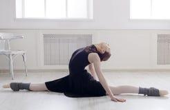 Classical Ballet dancer portrait. Beautiful graceful ballerine in black practice split ballet position in class room background. Ballet class training, high Royalty Free Stock Photography
