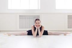 Classical ballet dancer portrait in white dansing hall. Beautiful ballerina doing side splits and smiling on camera. Classical ballet dancer at dancing class in Stock Images