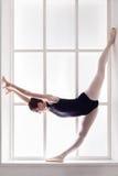 Classical Ballet dancer in split, ballerina at window sill. Ballerina show standing split at window sill background. Classical ballet training royalty free stock images