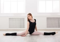 Classical ballet dancer in split in white dansing hall Royalty Free Stock Photography