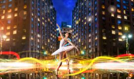Classical ballet dancer dancing on city road. Classical ballet dancer in white dress dancing on city road, cityscape with long exposure light effect. Graceful Royalty Free Stock Photo