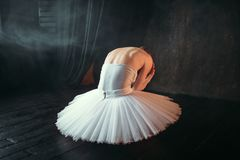 Ballet dancer sitting on stage, back view. Classical ballet dancer in white dress sitting on theatrical stage, back view. Ballerina training in class with black Stock Photos