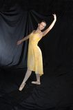 Classical Ballet Pose. A young ballerina poses in a graceful, classical pose while wearing a lyrical yellow dress Royalty Free Stock Photos