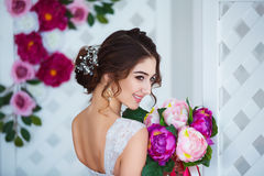 Classical beauty. Beautiful young woman with stylish brunette hair and elegant dress resting in luxury white classic Royalty Free Stock Photo