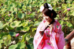 Classical beauty in China. A girl in Chinese ancient dress. She sits by the lotus pool,she is so beautiful and lovely Stock Photos