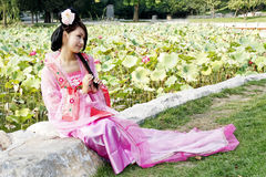 Classical beauty in China. A girl in Chinese ancient dress. She sits at the bank of the lotus pool, she is so beautiful and lovely Royalty Free Stock Image