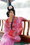Classical beauty in China. A beauty in Chinese ancient dress.She sat on board to enjoy the scenery Stock Photography