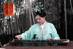 Classical beauty in China. A beautiful girl in Chinese ancient dress plays the zither in the ancient garden Stock Images