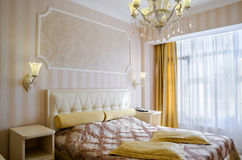 Classical bedroom with a large double bed, bedside tables, chairs Royalty Free Stock Images