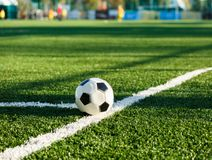 Classical black and white football ball on the green grass of the field stock photos