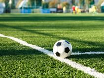 Classical black and white football ball on the green grass of the field. Soccer game, training, hobby concept royalty free stock images