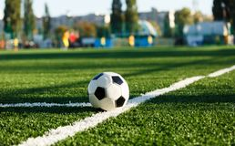 Classical black and white football ball on the green grass of the field. Soccer game, training, hobby concept. stock photos
