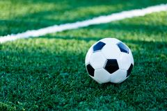 Classical black and white football ball on the green grass of the field. Soccer game, training, hobby concept. stock photo