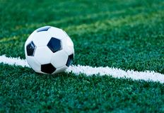 Classical black and white football ball on the green grass of the field. Soccer game, training, hobby concept. stock photography