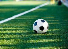 Classical black and white football ball on the green grass of the field stock image