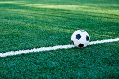 Classical black and white football ball on the green grass of the field. royalty free stock image