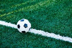 Classical black and white football ball on the green grass of the field. Soccer game, training, hobby concept. With copy space royalty free stock photo