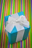 Classical blue gift box with white bow on colored striped backgr Royalty Free Stock Photo
