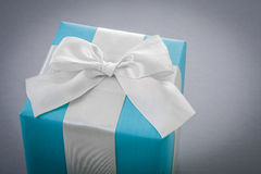Classical blue giftbox with white ribbon on gray background Stock Image