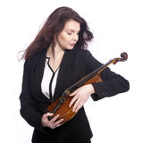 Classical brunette beauty in suit holds violin in studio Royalty Free Stock Photos