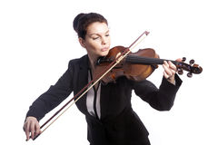 Classical brunette beauty in suit plays the violin in studio Royalty Free Stock Photography