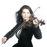 Classical brunette beauty in suit plays the violin in studio Stock Image