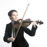 Classical brunette beauty in suit plays the violin in studio Stock Photo