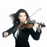 Classical brunette beauty in suit plays the violin in studio Stock Photos