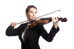 Classical brunette beauty in suit plays the violin in studio Stock Photography