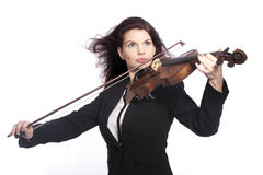 Classical brunette beauty in suit plays the violin in studio Royalty Free Stock Photo