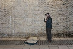 Classical busker standing against a brick wall Royalty Free Stock Images