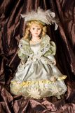 Classical ceramic doll. On brown hangings Stock Photo