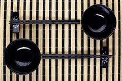 Classical chopsticks and black bowls Stock Photos