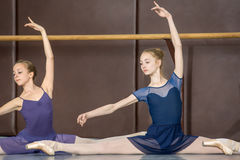 Classical choreography. Young ballerinas on the lesson of classical choreography sitting in the splits gracefully raising his hands up near barre stock photo