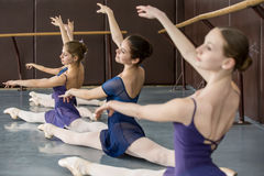 Classical choreography. Young ballerinas on the lesson of classical choreography sitting in the splits gracefully raising his hands up near barre stock photos