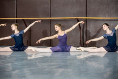 Classical choreography. Young ballerinas on the lesson of classical choreography sitting in the splits gracefully raising his hands up near barre stock images