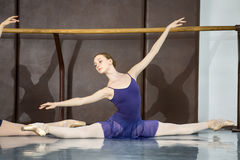 Classical choreography. Young ballerinas on the lesson of classical choreography sitting in the splits gracefully raising his hands up near barre royalty free stock image