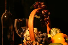 Classical composition: glass with fruit. Classical composition: glasses with basket of grapes and vegetables Royalty Free Stock Photos