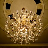 Classical crystal chandelier hanging on beautiful ceiling Stock Image
