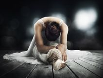 Classical dancer stretching on a stage of theater. Classical dancer doing stretching on a stage of theater