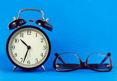 Classical desk clock,glasses on a blue background. Royalty Free Stock Image